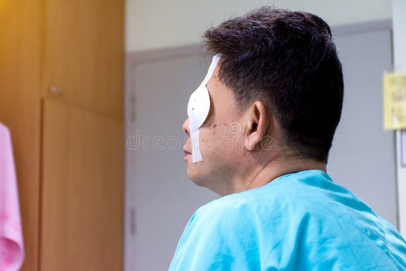 Uomini che si siedono ed utilizzare protezione dello schermo dell'occhio dopo la chirurgia dell'occhio nella stanza di ospedale immagini stock