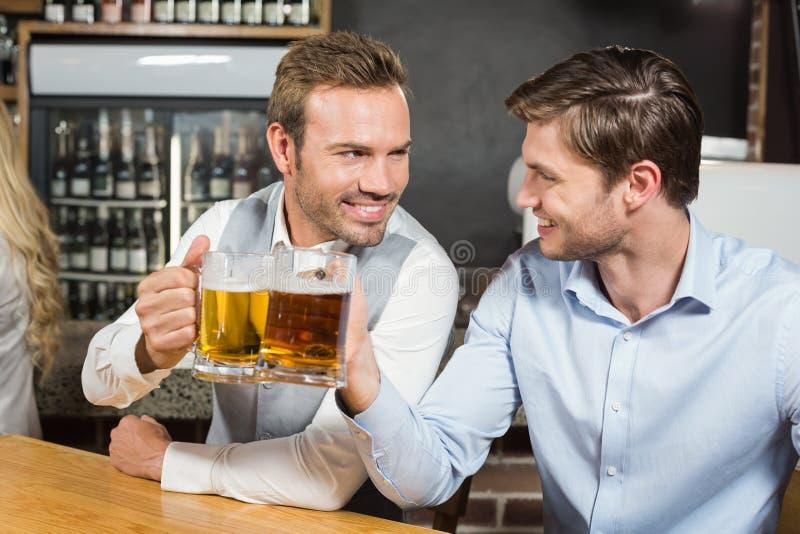 Uomini che tostano mentre esaminandose fotografia stock libera da diritti