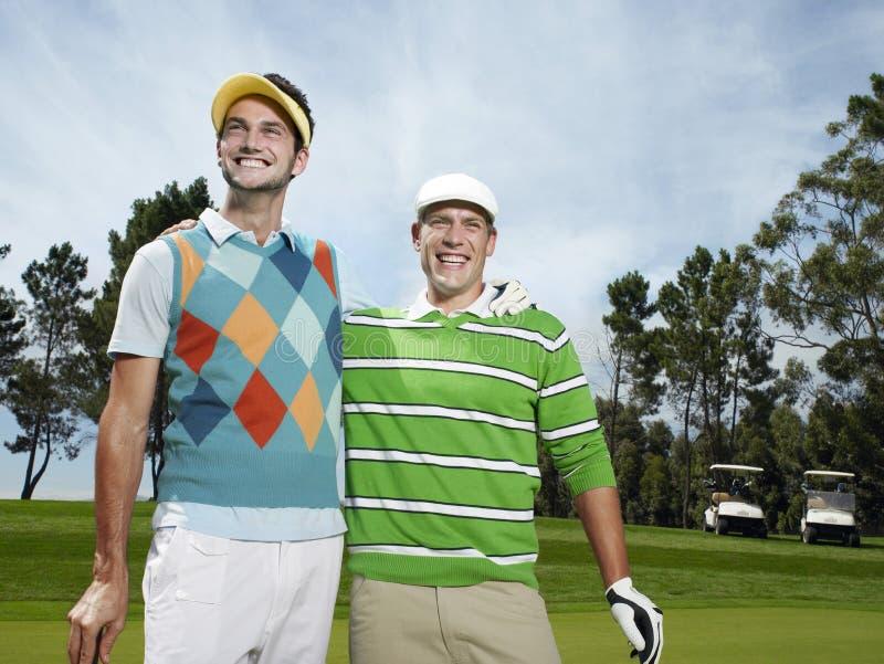Uomini con il braccio intorno al campo da golf fotografia stock libera da diritti