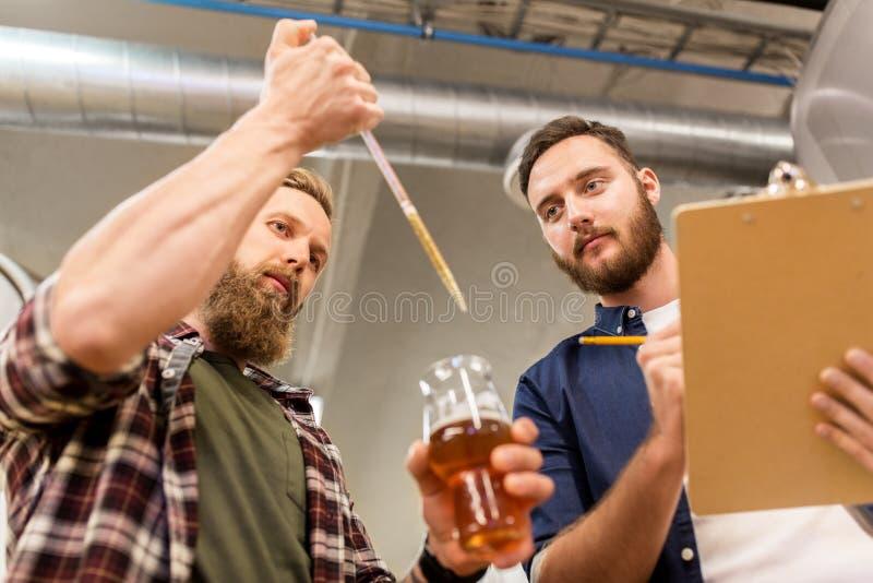 Uomini con la birra del mestiere di prova della pipetta alla fabbrica di birra fotografia stock libera da diritti