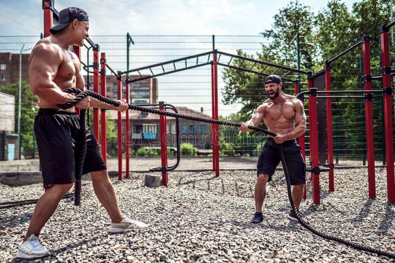 Uomini con la corda, addestramento funzionale immagine stock libera da diritti