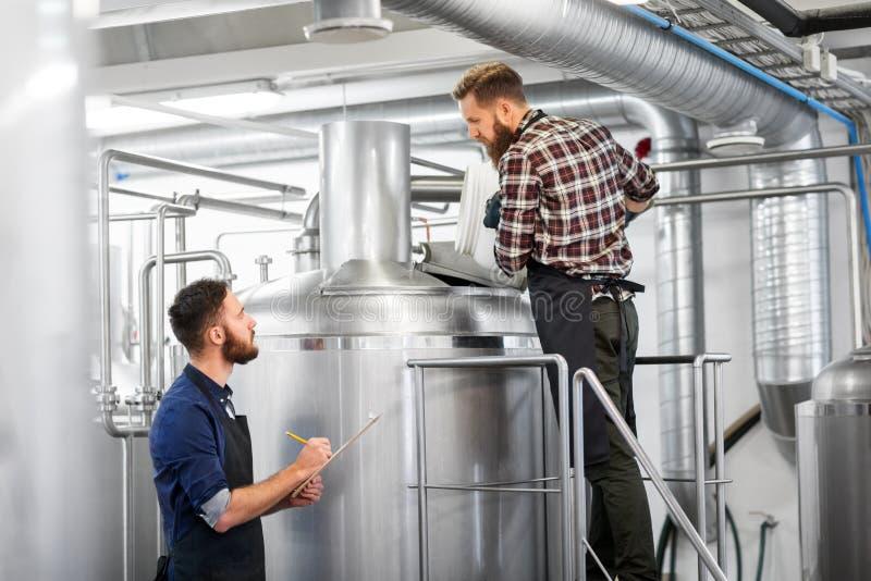 Uomini con la lavagna per appunti nel bollitore della fabbrica di birra o nella pianta della birra fotografia stock
