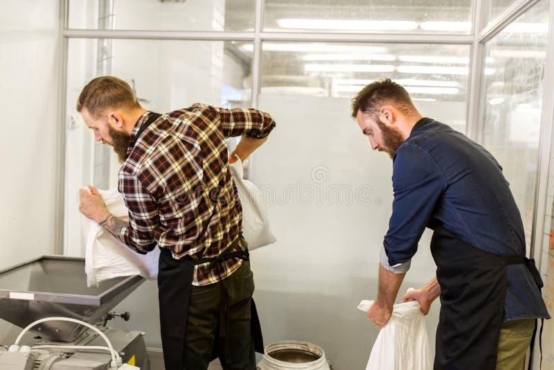 Uomini con le borse del malto e mulino alla fabbrica di birra della birra del mestiere fotografia stock libera da diritti