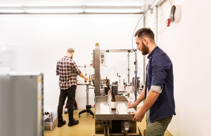 Uomini con le bottiglie sul trasportatore alla fabbrica di birra della birra del mestiere immagini stock libere da diritti