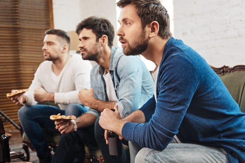 Uomini concentrati seri che guardano una partita di calcio fotografie stock libere da diritti