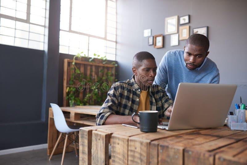 Uomini d'affari africani sul lavoro su un computer portatile in un ufficio immagine stock libera da diritti