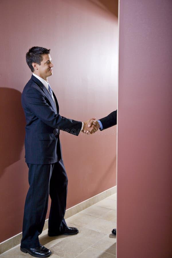 Uomini d'affari che agitano le mani in corridoio dell'ufficio immagini stock libere da diritti