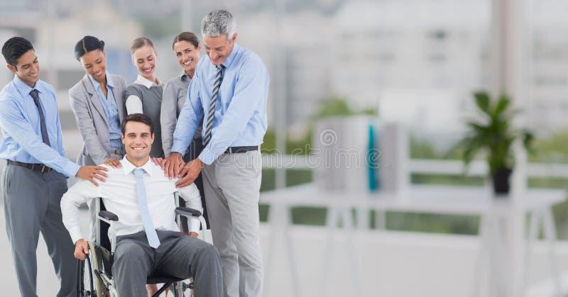 Uomini d'affari che consolano il loro collega che si siede sulla sedia a rotelle immagini stock libere da diritti
