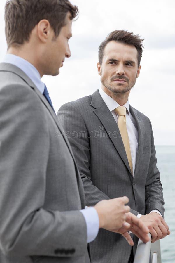 Uomini d'affari che hanno una discussione sul terrazzo fotografie stock libere da diritti