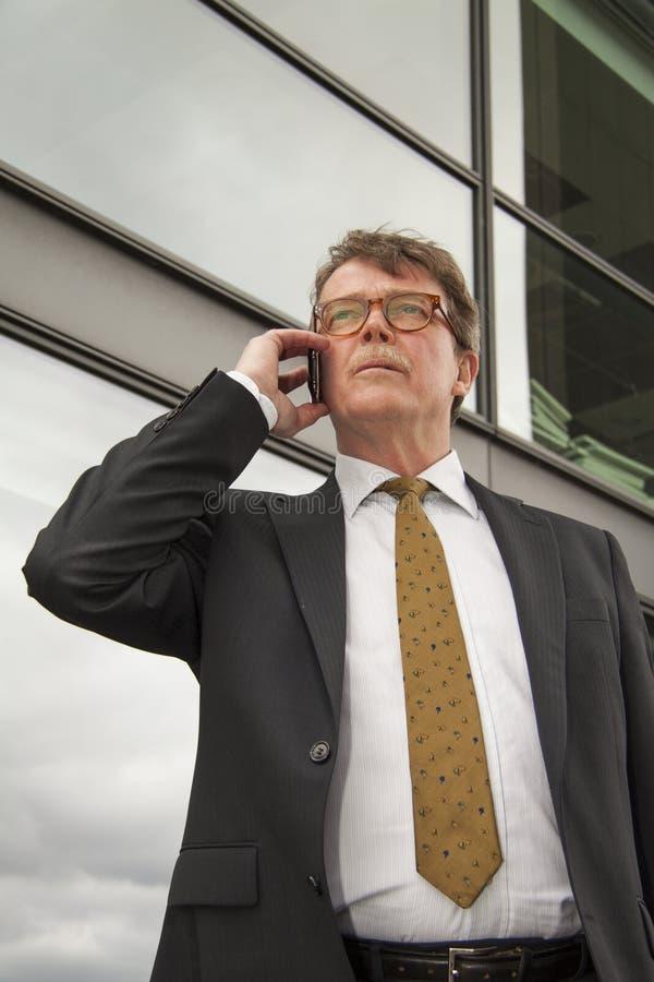 Uomini d'affari che parlano sul cellulare o sul telefono cellulare davanti all'edificio per uffici moderno fotografia stock