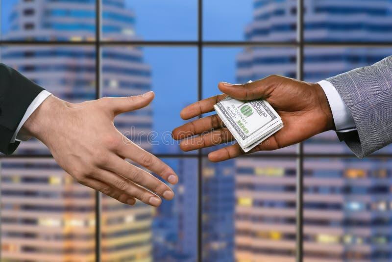 Uomini d'affari che passano i dollari americani immagini stock libere da diritti
