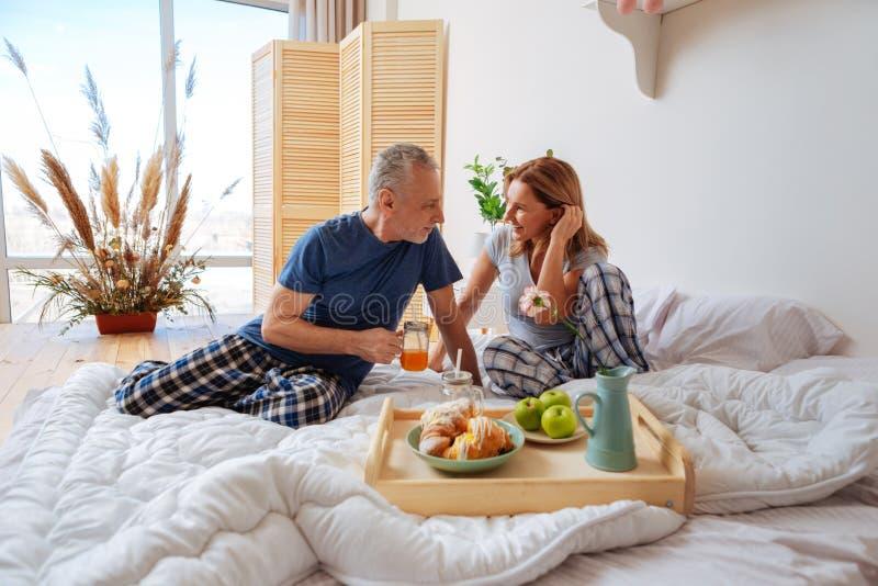 Uomini d'affari che portano i pigiami che godono della prima colazione di fine settimana a letto fotografie stock