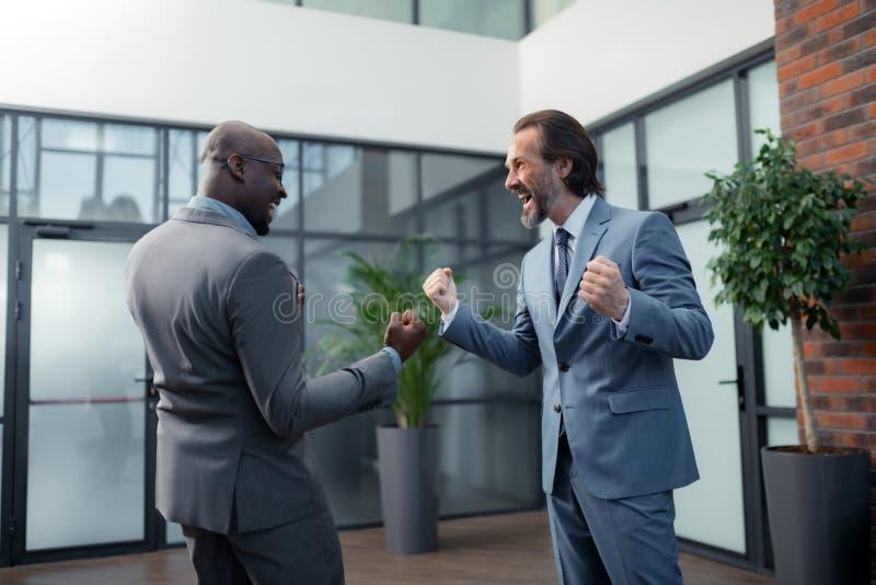 Uomini d'affari che ritengono estremamente felici dopo la riuscita riunione fotografie stock
