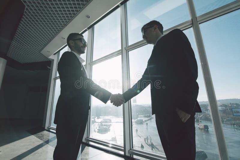 Uomini d 39 affari che stringono le mani dentro contro le - Uccelli che sbattono contro le finestre ...