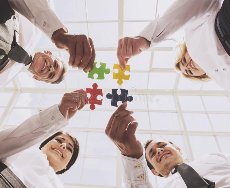 Uomini d'affari che tengono e che mettono i pezzi di puzzle immagine stock libera da diritti