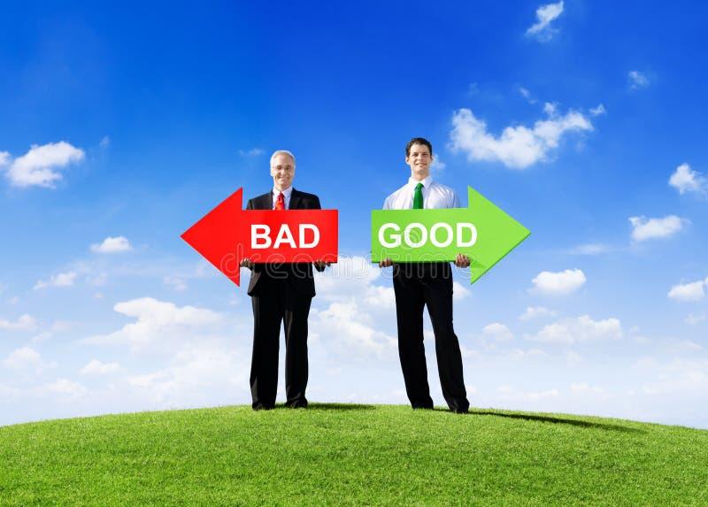 Uomini d'affari che tengono le frecce per cattivo e buon immagine stock libera da diritti