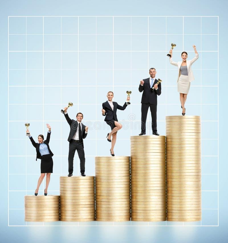 Uomini d'affari che tengono tazza dorata sulla scala delle monete immagini stock libere da diritti