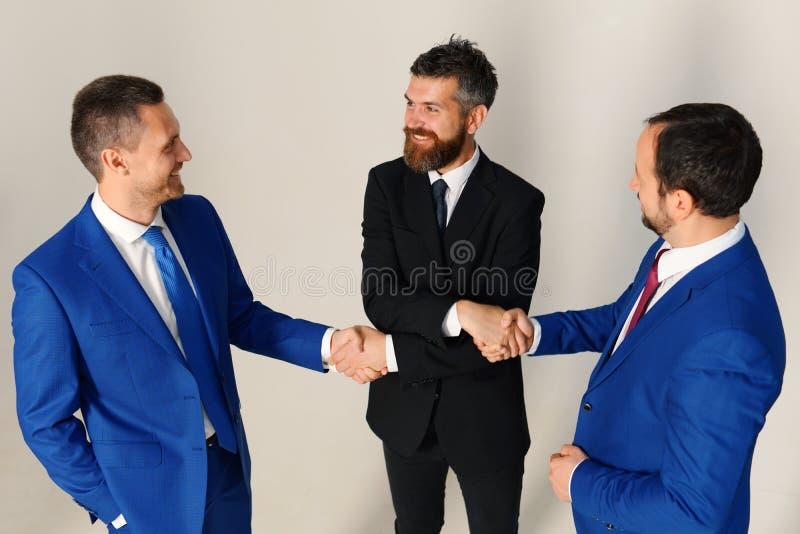 Uomini d'affari con i fronti felici in vestiti convenzionali Capi della società immagini stock libere da diritti
