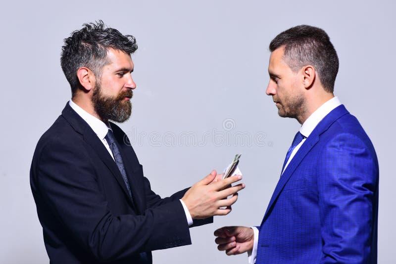 Uomini d'affari con i fronti occupati in vestiti convenzionali su fondo grigio immagini stock libere da diritti