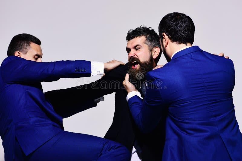 Uomini d'affari con i fronti pazzi in vestiti convenzionali su fondo grigio fotografie stock