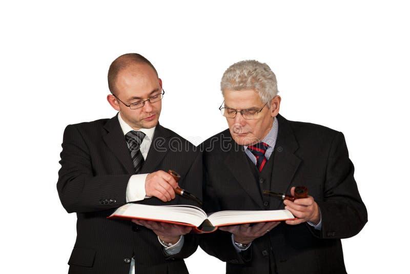 Uomini d'affari con i tubi che leggono un libro immagini stock