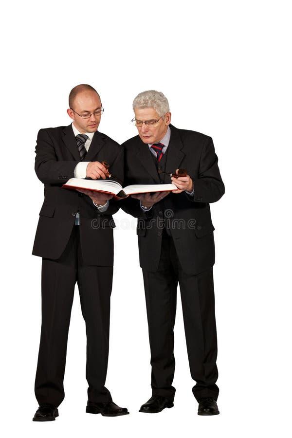 Uomini d'affari con i tubi che leggono un libro immagine stock libera da diritti
