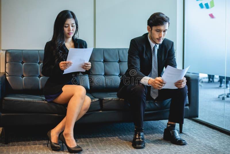 Uomini d'affari e donne di affari che discutono i documenti e le idee nel concetto di intervista di lavoro e di riunione fotografie stock libere da diritti