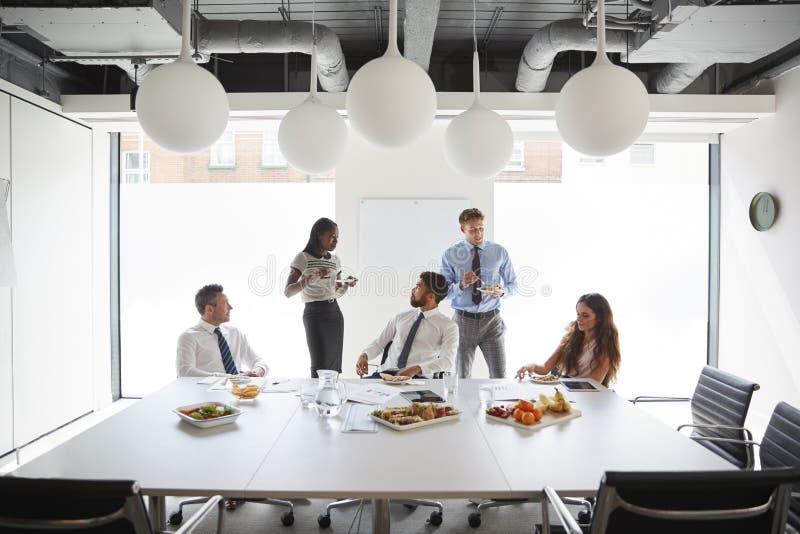 Uomini d'affari e donne di affari che si incontrano nella sala del consiglio moderna sopra colazione di lavoro immagini stock libere da diritti