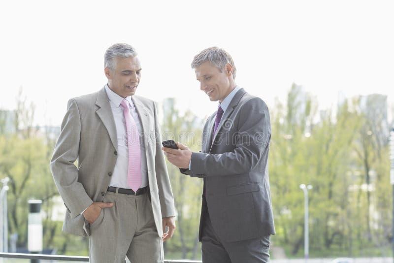 Uomini d'affari facendo uso del telefono cellulare insieme all'aperto immagine stock