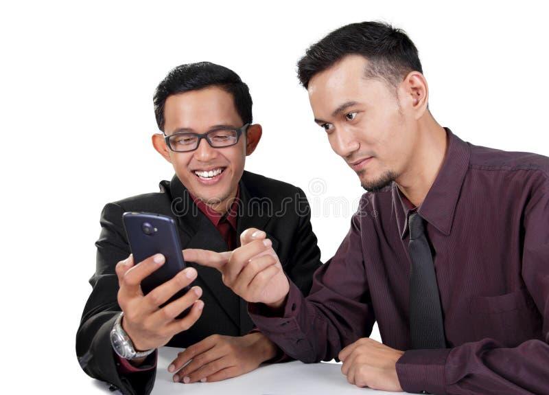 Uomini d'affari facendo uso dello smartphone fotografie stock