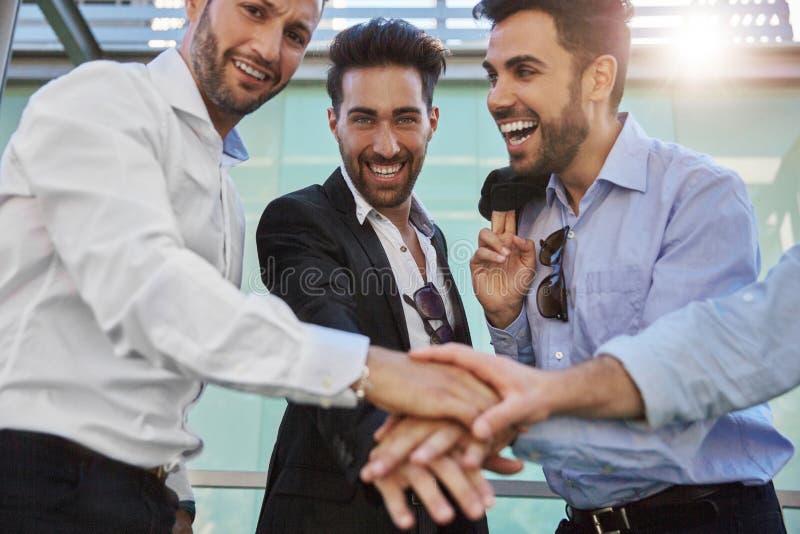 Uomini d'affari felici che si tengono per mano insieme risata fotografia stock
