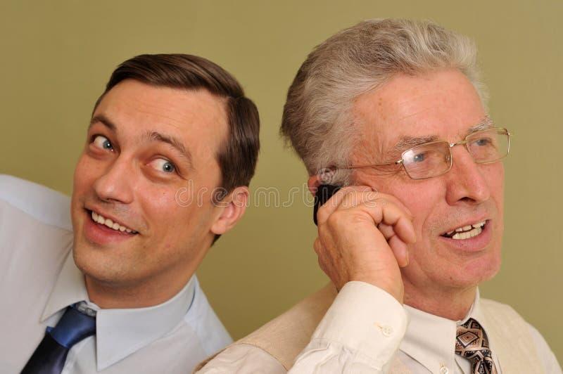 Uomini d'affari insieme e comunicando sul telefono fotografie stock libere da diritti