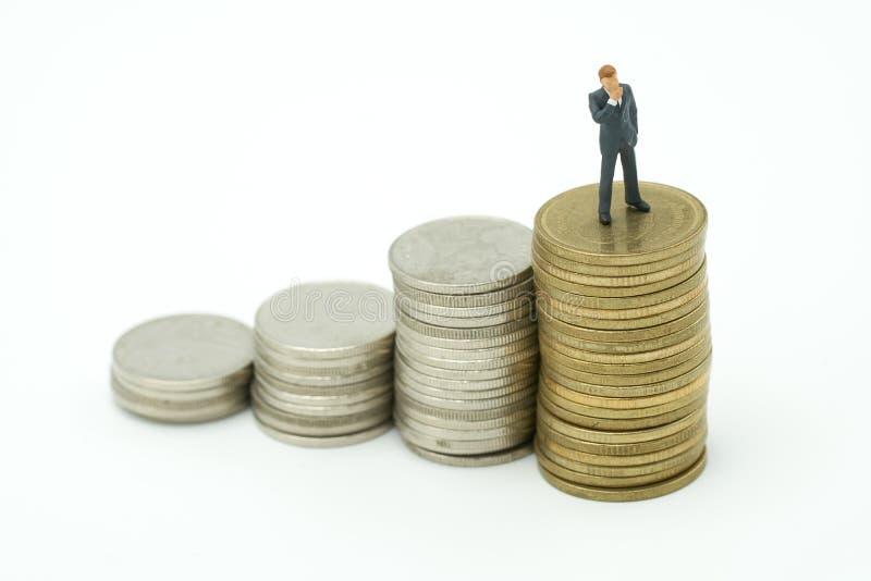 Uomini d'affari miniatura della gente che stanno analisi degli investimenti o inv fotografia stock libera da diritti