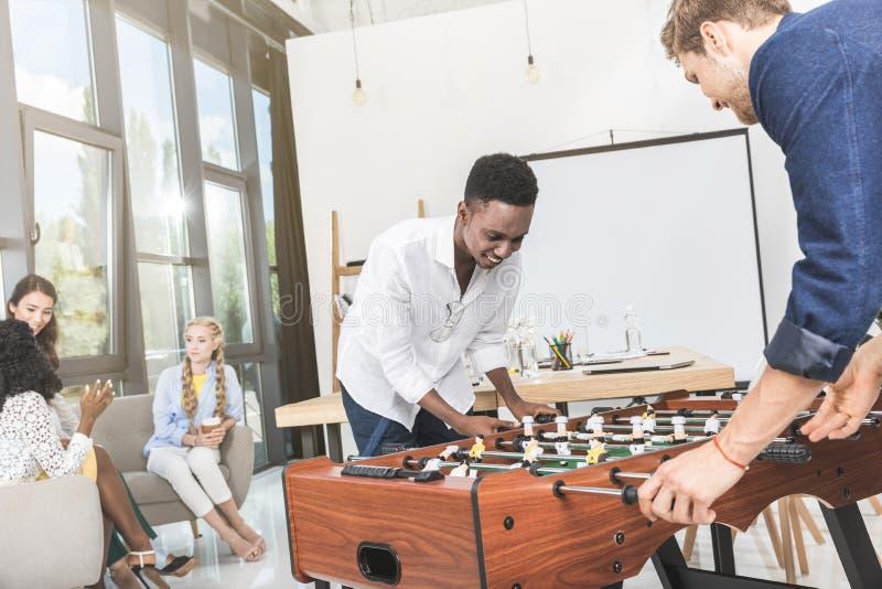 uomini d'affari multiculturali che giocano calcio-balilla mentre donne di affari che hanno conversazione durante la pausa fotografie stock