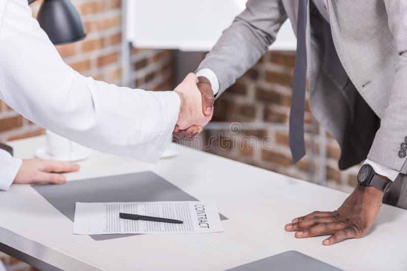 Uomini d'affari multietnici che stringono le mani prima della firma del contratto fotografia stock libera da diritti
