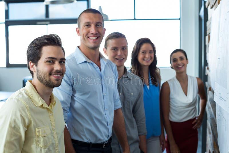 Uomini d'affari sorridenti che stanno nell'ufficio fotografie stock
