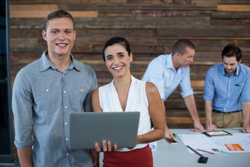 Uomini d'affari sorridenti che stanno nell'ufficio con il computer portatile fotografie stock