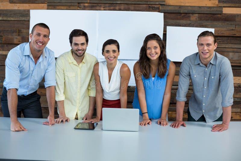 Uomini d'affari sorridenti che stanno nell'ufficio con il computer portatile sulla tavola immagini stock libere da diritti