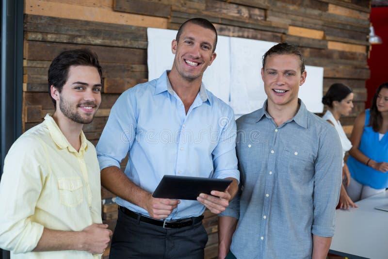 Uomini d'affari sorridenti che stanno nell'ufficio con la compressa digitale immagini stock