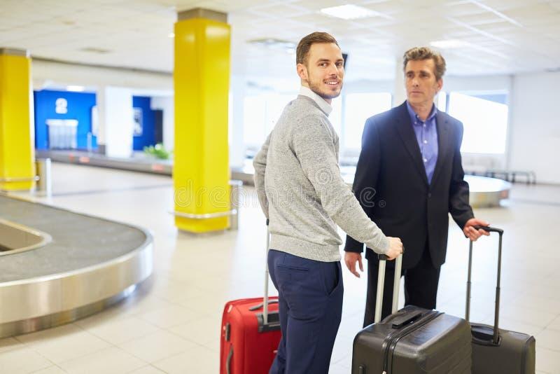 Uomini d'affari sul viaggio di affari al reclamo di bagaglio immagine stock libera da diritti