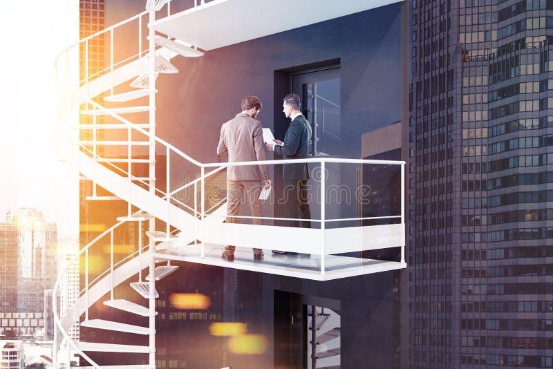 Uomini d'affari sulle scale dell'uscita di sicurezza, piano b fotografia stock