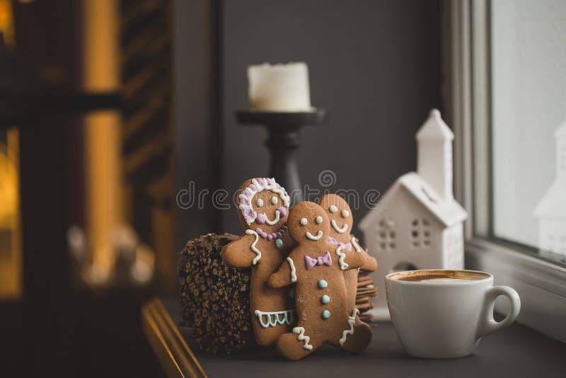 Uomini del biscotto del pan di zenzero in una tazza calda di cappuccino fotografia stock