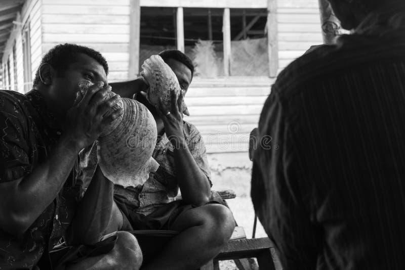 Uomini del Fijian che soffiano le conchiglie di strombo fotografia stock libera da diritti