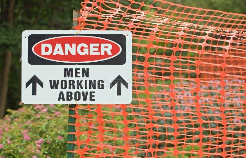 Uomini del pericolo che lavorano sopra fotografia stock