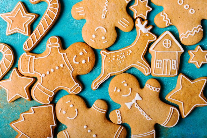 Uomini dello zenzero con la glassa colorata su un fondo del turchese gingerbread Biscotti di natale fotografia stock