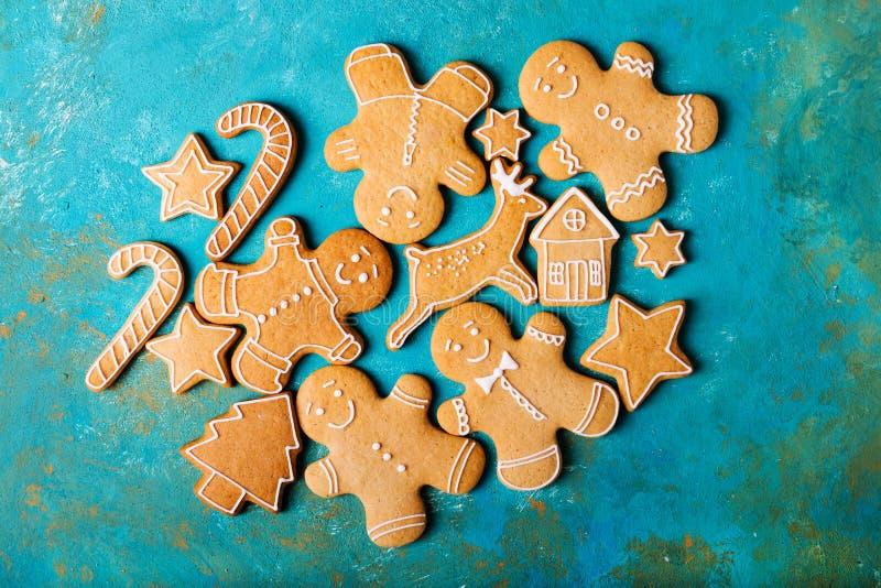 Uomini dello zenzero con la glassa colorata su un fondo del turchese gingerbread Biscotti di natale immagine stock