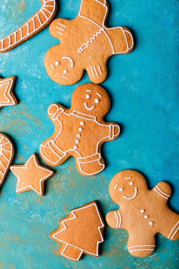 Uomini dello zenzero con la glassa colorata su un fondo del turchese gingerbread Biscotti di natale fotografia stock libera da diritti