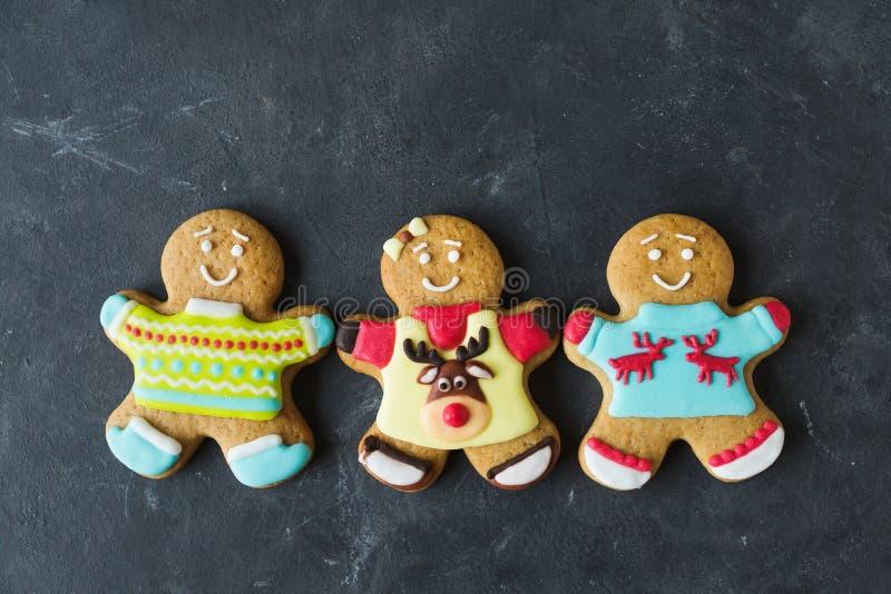 Uomini dello zenzero con la glassa colorata su un fondo grigio gingerbread Biscotti di natale fotografia stock libera da diritti