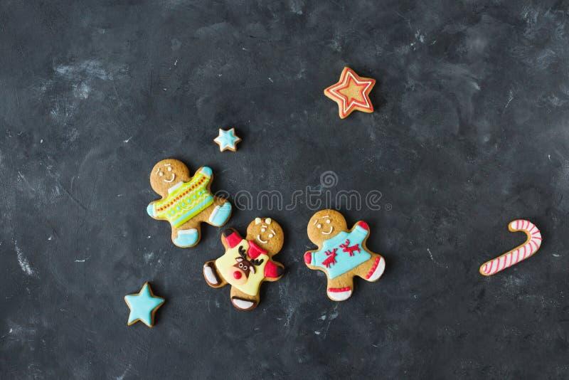Uomini dello zenzero con la glassa colorata su un fondo grigio gingerbread Biscotti di natale fotografia stock