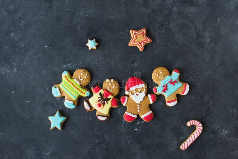 Uomini dello zenzero con la glassa colorata su un fondo grigio gingerbread Biscotti di natale immagine stock libera da diritti
